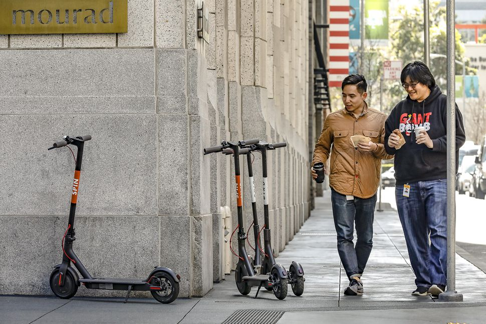 Two pedestrians taking note of a group of scooters on an SF sidewalk.